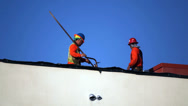 Stock Video Footage of Construction workers install the roof at development site