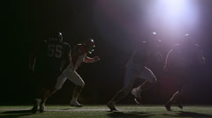Football players run a play and a receiver catches the ball. Silhouette Stock Footage