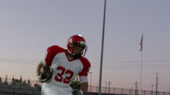A football player runs past multiple defenders as he tries to score Stock Footage