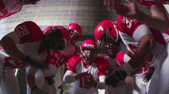 A team of football players huddle and clap to get hyped and ready for the game Stock Footage