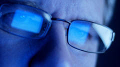 Computer screen and code reflected in man's glasses - stock footage