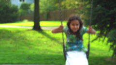 Cute little girl on a swing smiles for the camera - stock footage