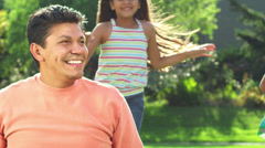 Girls run up behind their dad and jump on his back - stock footage