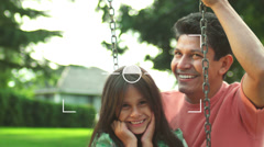 Taking a photograph of a father pushing his daughter on a swing Stock Footage
