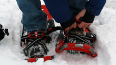Man putting on snowshoes Stock Footage