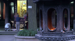 Lantern with a flame with people praying to buddha at the background Stock Footage