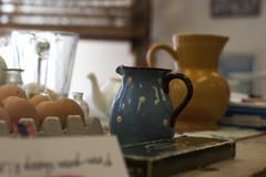A table top of colourful clutter of jugs, teapots, bit and bobs Stock Photos