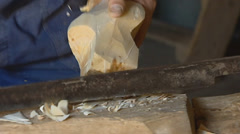 Carving modeling the heel of a wooden shoe with a oblong knife Stock Footage