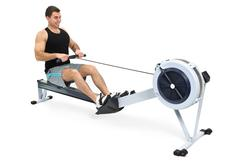 man doing exercises on rowing machine, on white background - stock photo