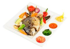 fried wish with grilled vegetables, pickled ginger, chukka seaweed etc - stock photo