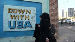 Iran, Down with USA mural painting, veiled women, former US Embassy, Tehran - stock footage