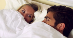 Cute couple hiding under the sheets - stock footage