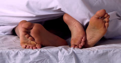 Couples feet wiggling under the duvet - stock footage