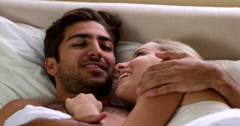 Cute couple conversing in bed - stock footage