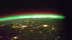 ISS (International Space Station) orbiting earth with visible aurora borealis - stock footage