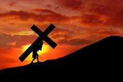 christian background - man carrying a cross up hill - stock photo