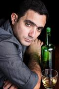 Lonely and sad hispanic man drinking alone Stock Photos