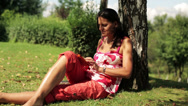 Stock Video Footage of woman sitting with a tablet under the tree