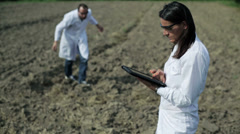 Couple of scientists working with tablet in the field Stock Footage