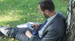 Businessman using cellphone and sitting under the tree Stock Footage