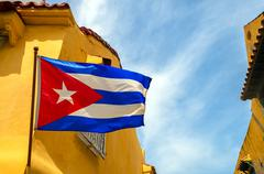 cuban flag and colonial buildings - stock photo