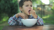 Stock Video Footage of little boy eating soup with fingers by the table in the garden