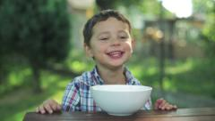 Stock Video Footage of little boy eating soup by the table in the garden