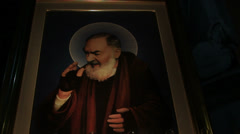 Padre Pio in a dark church Stock Footage