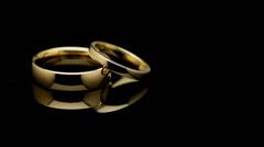 Pair of wedding rings turning on black Stock Footage