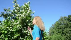 Girl in blue sweater pick jasmin bush white blooms in summer Stock Footage