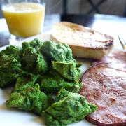 Green scrambled eggs and ham breakfast, orange juice Stock Photos