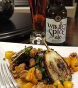 Hearty spicy eggplant sausage dish on white plate and beer Stock Photos