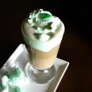 Irish coffee with green whipping cream, sprinkles and candies Stock Photos
