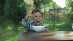Little boy eating soup by the table in the garden Stock Footage