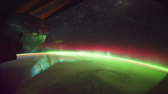 ISS (International Space Station) orbiting earth above red and green Aurora  Stock Footage
