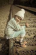 Stock Photo of small girl seating on railroad tracks, india