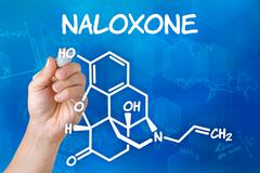 Hand with pen drawing the chemical formula of naloxone Stock Illustration