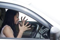 angry female driver driving a car - stock photo