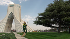 Tehran, using a broom to sweep grass from pathway, Azadi Tower Stock Footage