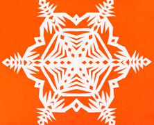 White snowflake on orange paper Stock Photos
