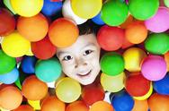 Stock Photo of cheerful boy with colorful balls