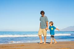 Happy father and son walking together on the beach, carefree happy fun smilin Stock Photos