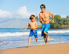 happy father and son playing and running together at beach - stock photo