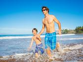 Stock Photo of happy father and son walking together at beach