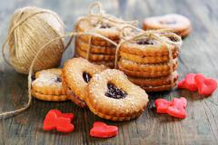 red marzipan hearts, cookies and ball of twine. - stock photo