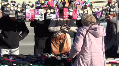 Zoom out vendor woman sell gloves and people size them in market Stock Footage