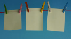 Sticky yellow papers notes hanging on clothes peg, on a blue background. - stock footage