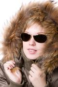 playful girl with sunglasses in a jacket with a collar of fur - stock photo
