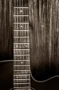 detail of acoustic guitar in vintage style on wood background - stock photo