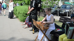 Girl play Baltic psaltery string instrument and people in street Stock Footage